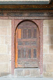 Wooden aged vaulted door and stone wall Royalty Free Stock Photo