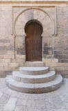 Wooden aged vaulted door, three steps and stone wall Royalty Free Stock Photography