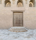 Wooden aged vaulted door, threee ornate engraved vaulted windows stock images