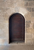 Wooden aged vaulted ornate door and stone wall Stock Images