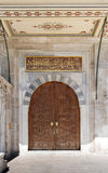 Wooden aged vaulted ornate door and stone wall at Sulaymaniye Mosque, Istanbul Royalty Free Stock Image