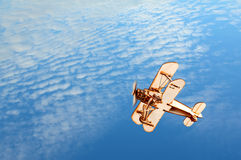 Wooden airplane in the blue sky. Wooden toy airplane in the blue sky royalty free stock image