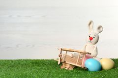 Wooden airplane with cute Easter bunny toy and dyed eggs on green grass. Space for text royalty free stock photo