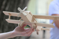 Wooden airplane in hand. On blurry background Stock Photography