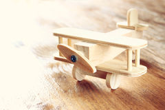 Wooden airplane toy over textured wooden background. retro style image.  stock photo