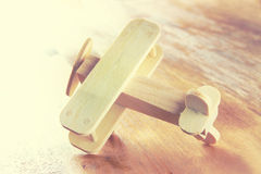 Wooden airplane toy over textured wooden background. retro style image.  royalty free stock image