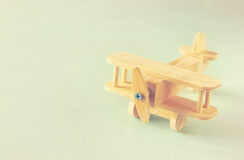 Wooden airplane toy over textured wooden background. retro style image Royalty Free Stock Photos