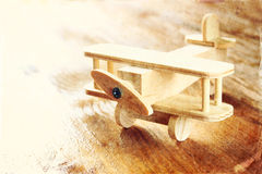 Wooden airplane toy over textured wooden background. retro style image.  stock image