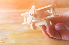 Wooden airplane toy over textured wooden background. retro style image.  royalty free stock photo