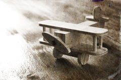 Wooden airplane toy over textured wooden background. retro style image. black and white old style photo.  stock photography