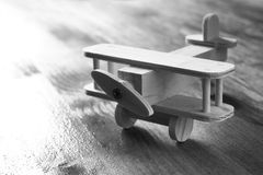 Wooden airplane toy over textured wooden background. retro style image. black and white old style photo.  stock images