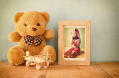 Wooden airplane toy and teddy bear over wood table next to photo frame with kid's old photography. retro filtered image Royalty Free Stock Photos