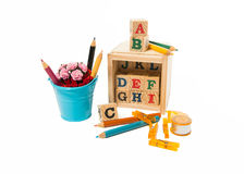 Wooden alphabet block with color pencil, clips, tape, and blue bucket of flower Royalty Free Stock Image