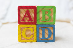 Wooden Alphabet Blocks on Quilt Spelling ABCD Stacked Stock Images