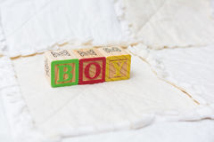 Wooden Alphabet Blocks on Quilt Spelling Boy Far Away Stock Photos