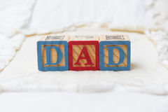 Wooden Alphabet Blocks on Quilt Spelling Dad Royalty Free Stock Photo
