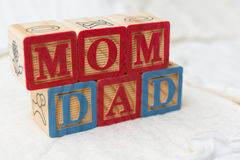 Wooden Alphabet Blocks on Quilt Spelling Mom and Dad Stock Photos