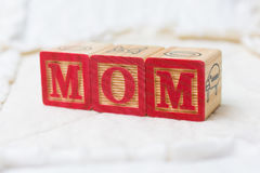 Wooden Alphabet Blocks on Quilt Spelling Mom Royalty Free Stock Photo