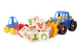 Wooden alphabet blocks with a toy tractors Royalty Free Stock Image