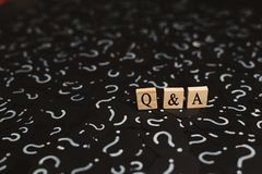 Wooden alphabet tiles with Q&A letter on black paper with QUESTION MARK. Concept of Question and Answer Q&A online assist royalty free stock images