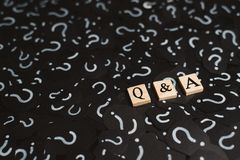 Wooden alphabet tiles with Q&A letter on black paper with QUESTION MARK. Concept of Question and Answer Q&A online assist stock images