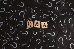 Wooden alphabet tiles with Q&A letter on black paper with QUESTION MARK. Concept of Question and Answer Q&A online assist stock photos