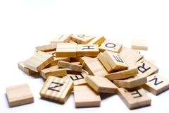 The wooden alphabets with a black letters on the brown wood, this image on white background. For wallpaper, display or backdrop royalty free stock image