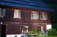 Wooden Alpine lodge with flower pots on the front lawn Royalty Free Stock Photo