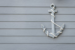 Wooden anchor on wood wall. Background stock image