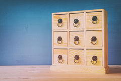 Wooden antique chest with drawers and metal handles. Image of natural wooden antique chest with drawers and metal handles. Filtered and toned stock photography