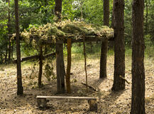 Wooden arbor with camouflage. In the pine forest Stock Images