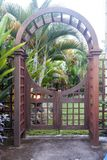 Wooden arbor with close gate in garden. Wooden arched entrance to the backyard. Wooden arbor with close gate in garden. Wooden arched entrance to the backyard Royalty Free Stock Images