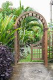 Wooden arbor with close on half gate in garden. Wooden arched entrance to the backyard. Wooden arbor with close on half gate in garden. Wooden arched entrance Royalty Free Stock Image