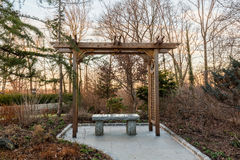 Wooden arbor in forest with stone seat. Polished granite seat under a wooden arbor or gazebo in woods at sunset in winter Royalty Free Stock Photo