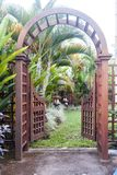 Wooden arbor with gate in garden. Wooden arched entrance to the backyard. Wooden arbor with gate in garden. Wooden arched entrance to the backyard Stock Photos