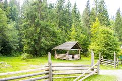 Wooden arbor near the forest. Behind the fence. Traditional ukrainian gazebo in Carpathian Mountains Stock Photos