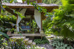 Wooden arbor for relaxing in tropical garden. Island Bali, Ubud, Indonesia. Wooden arbor for relaxing in the tropical garden. Island Bali, Ubud, Indonesia stock photo