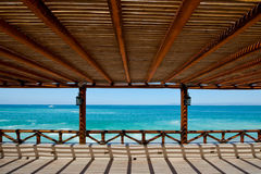 Wooden arbor and sea. Scenic view of turquoise sea viewed from underneath wooden arbor and terrace Stock Image
