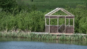 Wooden arbor on shore of pond stock footage