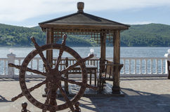 Wooden arbor with table and decorative helm on the Angara river shore Stock Images