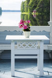 Wooden arbor. Table with flowers and lake, Finland Royalty Free Stock Photo