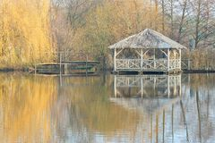 Wooden arbour in autumn by a lake with reflections. In the clear water Royalty Free Stock Photo