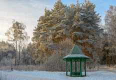 Wooden arbour covered with hoarfrost in winter garden. Trees and wooden arbour covered with hoarfrost in winter garden Stock Image