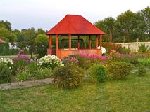 Wooden arbour in floral garden at sunset. Wooden gazebo in floral garden at sunset Stock Photos