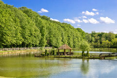 Wooden arbour on green lake Stock Image