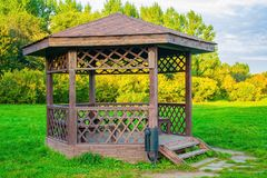 Wooden arbour in park a background of green trees Stock Image