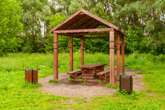 Wooden arbour a background of green trees. Wooden arbour in park with table, benches and two garbage cans on the sides a background of green trees summer Royalty Free Stock Image