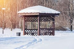 Wooden arbour in the snow-covered park. Illuminated by sunlight toned Royalty Free Stock Photo
