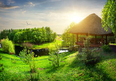 Wooden arbour. With thatched roof near river Stock Photos
