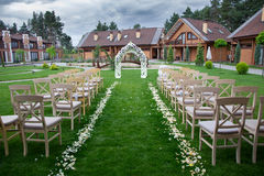 Wooden arch and chairs at wedding ceremony. Arch and wooden chairs at the wedding ceremony, green grass Stock Images